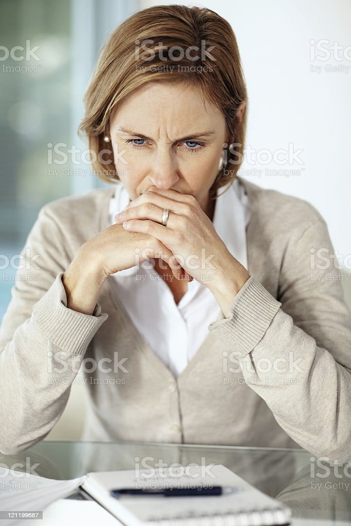 Disappointed mature businessswoman thinking about something stock photo