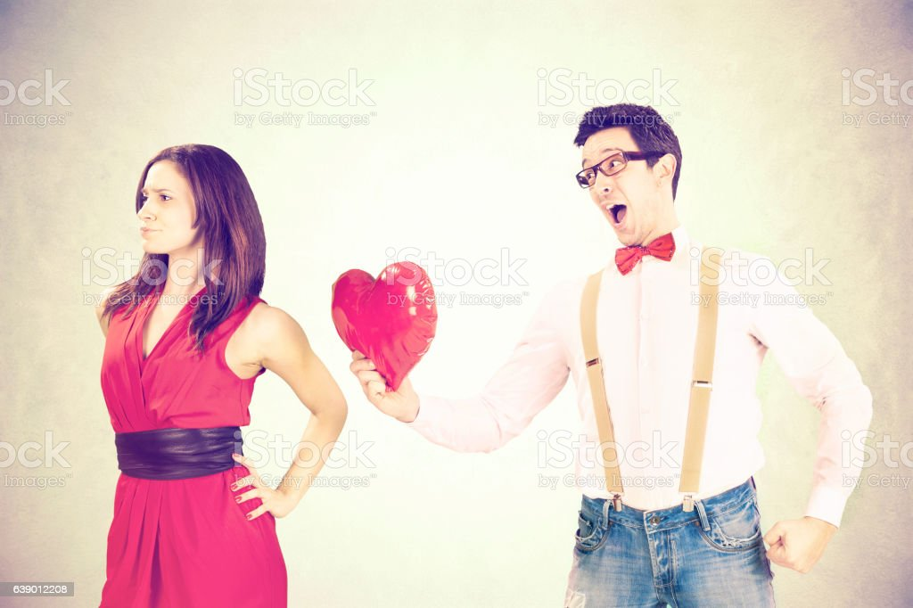 disappointed woman rejecting the red heart of her boyfriend stock photo