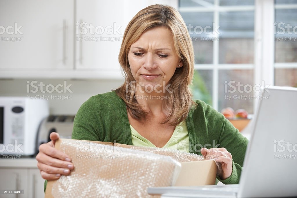 Disappointed Woman Unpacking Online Purchase At Home stock photo