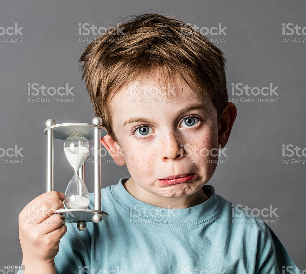 disappointed young boy with an hourglass for time concept stock photo