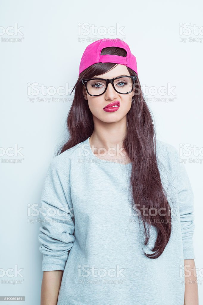 Disappointed young woman wearing nerd glasses and pink baseball cap stock photo