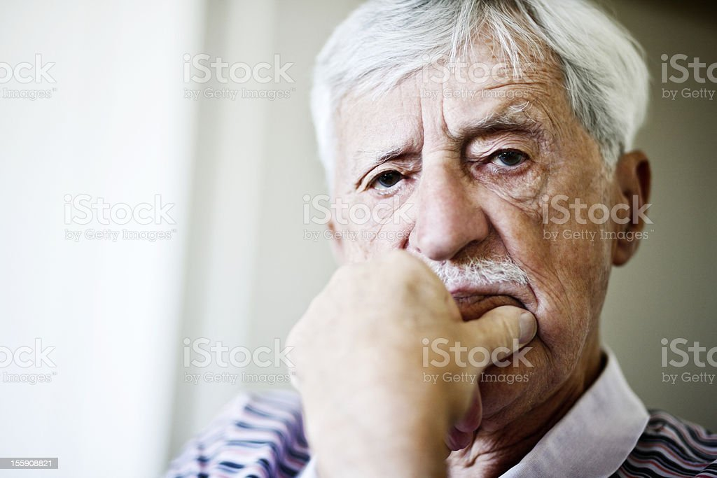 Disapproving old man stares out, hand on chin royalty-free stock photo