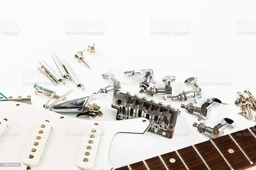 Disassembled electric guitar parts on workbench stock photo