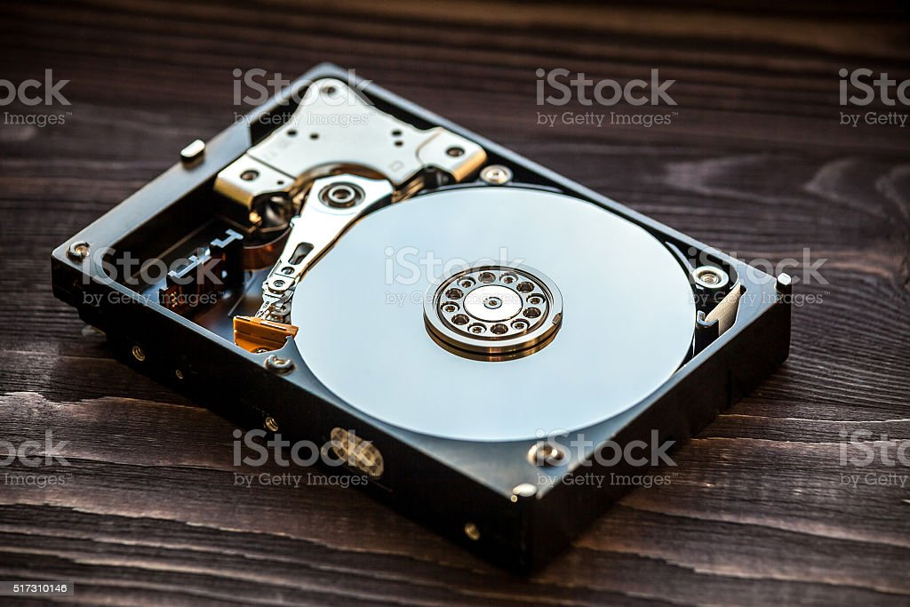 Disassembled HDD on the wooden rustic background close-up shot stock photo