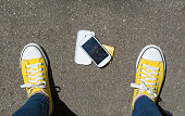 Disassembled smartphone on the ground in front of person