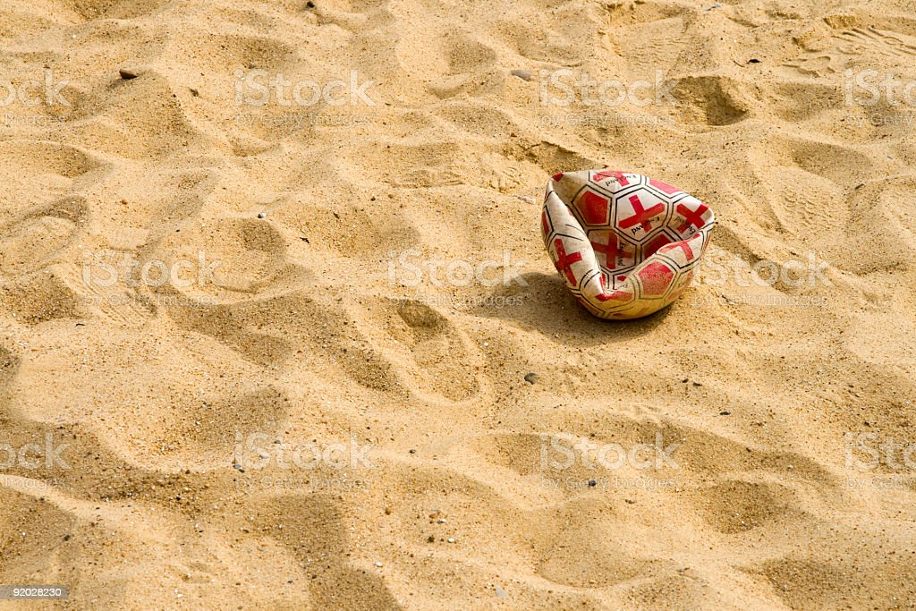 Disaster for England - punctured football on sand royalty-free stock photo
