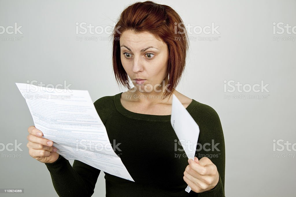 Disbelieved woman looking down at credit card statement stock photo