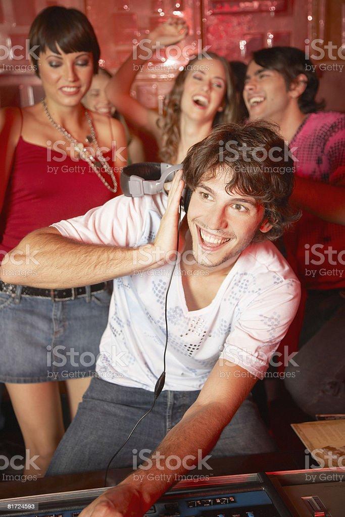Disc jockey in nightclub with people dancing around him smiling royalty-free stock photo