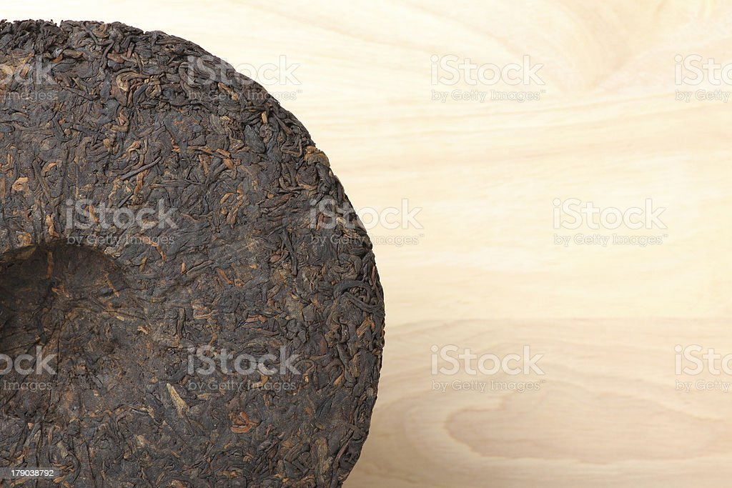 Disc of puer tea on wooden background royalty-free stock photo