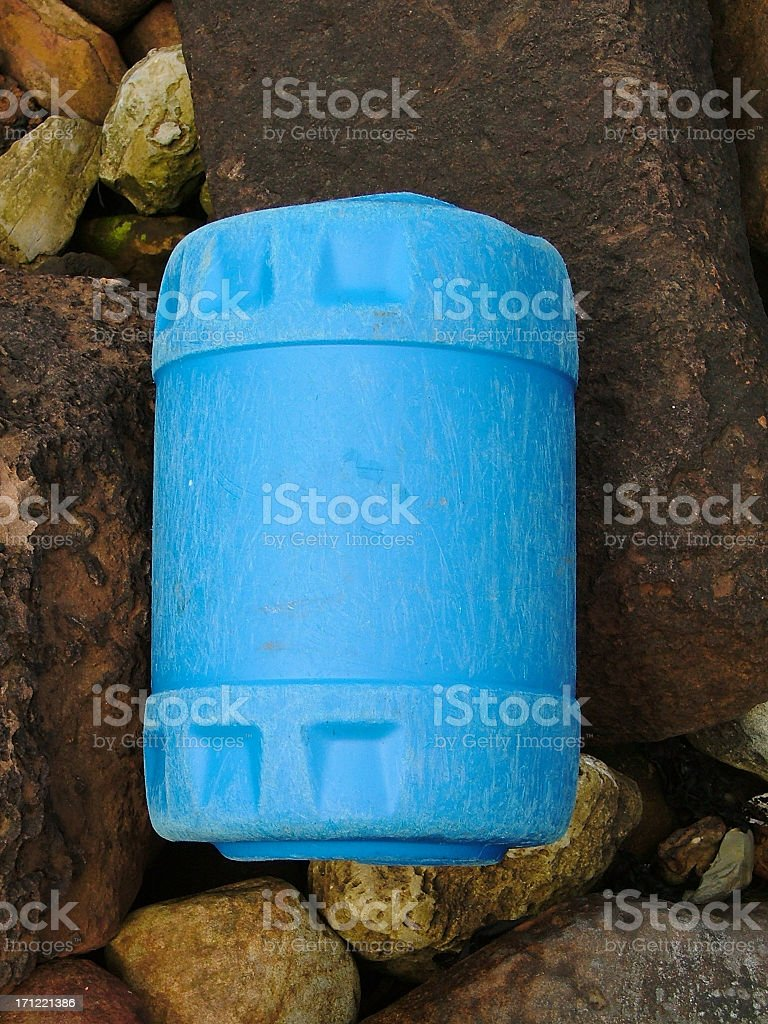 Discarded Blue Plastic Barrel on Rocks. stock photo