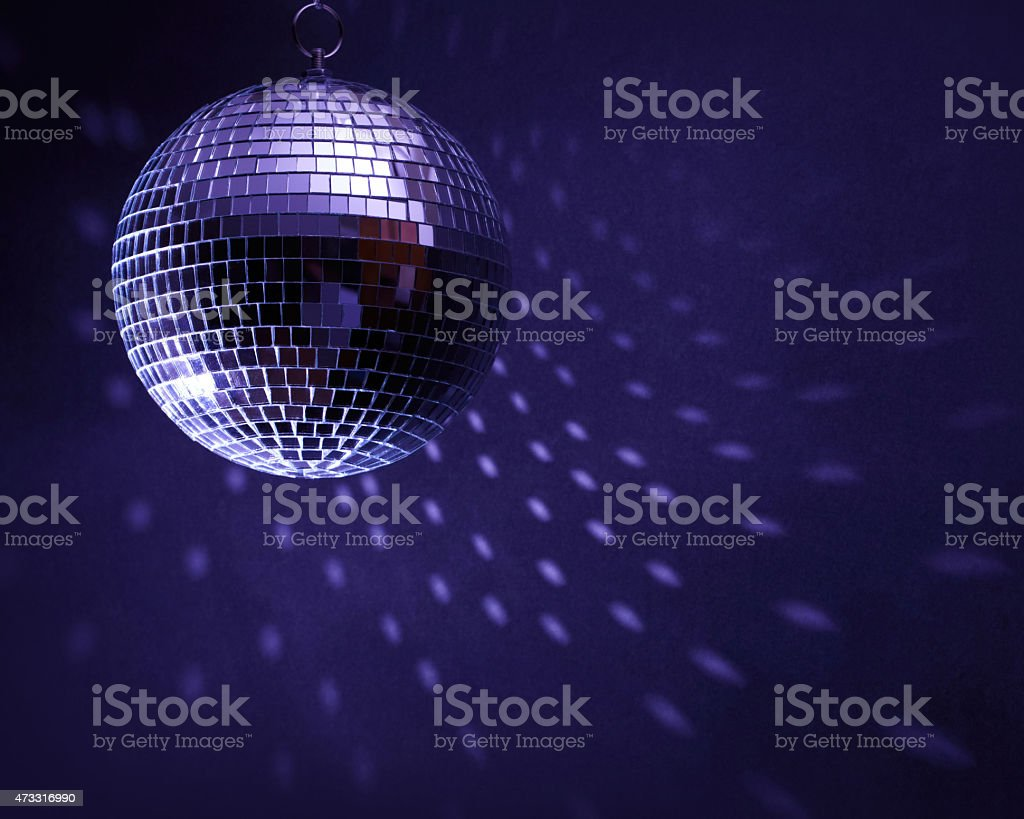 Disco ball in a dark room creating spots on the wall stock photo