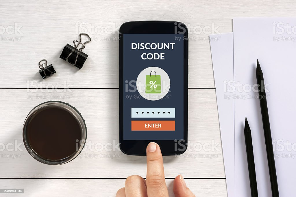 Discount code concept on smart phone screen with office objects stock photo