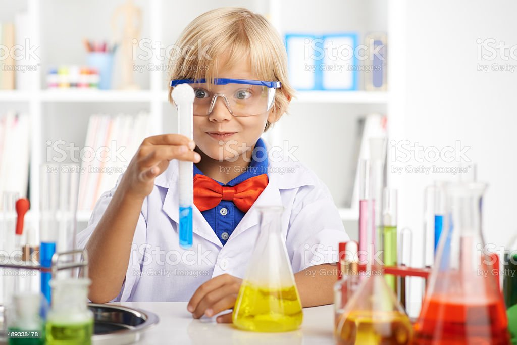 Excited little scientist looking at the foaming liquid in the...