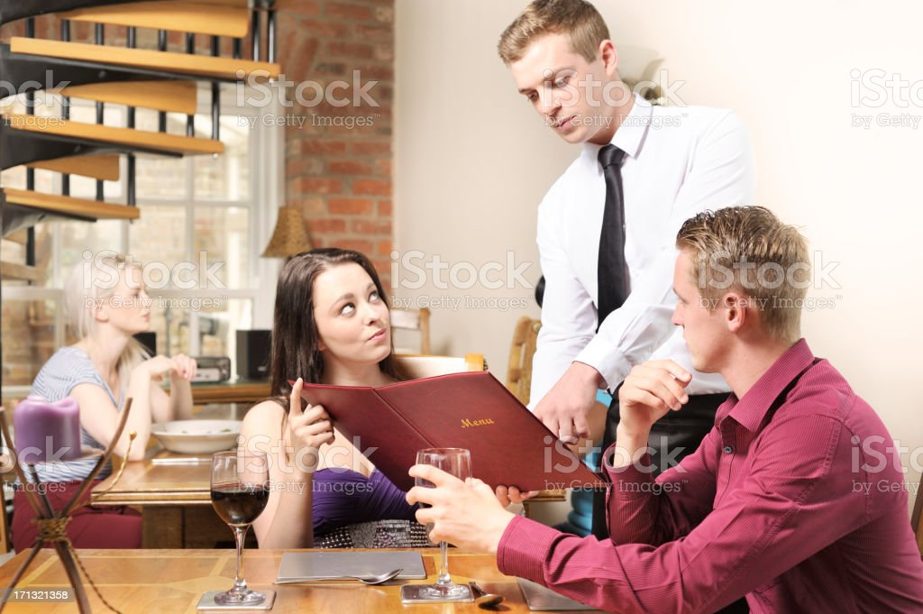 Discussing menu with waiter in restaurant stock photo