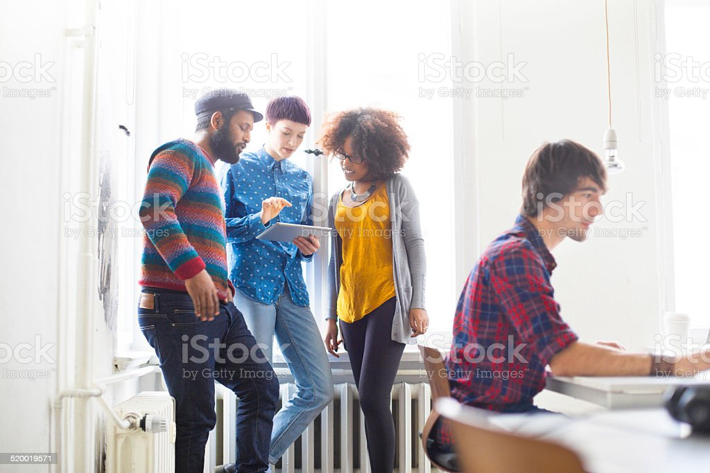 Discussing new business ideas on digital tablet stock photo