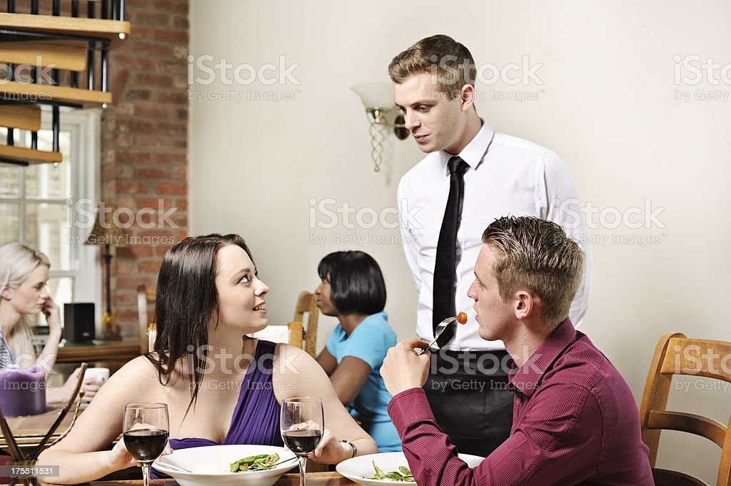 Discussing the meal with waiter in restaurant stock photo