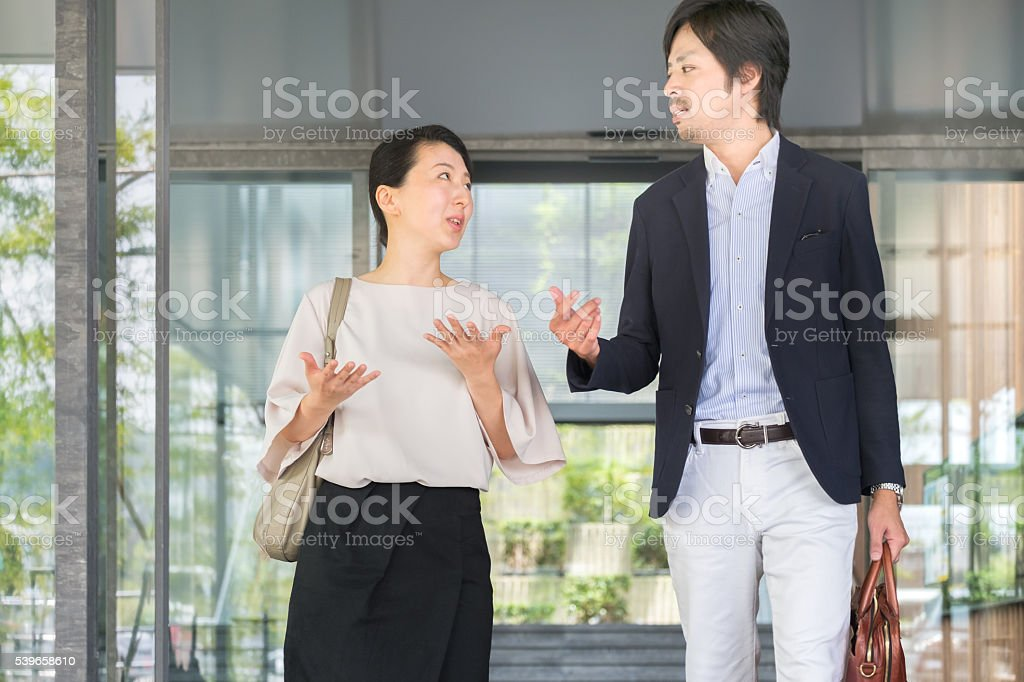 Discussion Between Japanese Businesswoman and Businessman Leaving Office Lobby Entrance stock photo