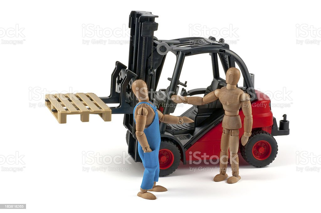 discussion in front of forklift - wooden mannequin at work royalty-free stock photo