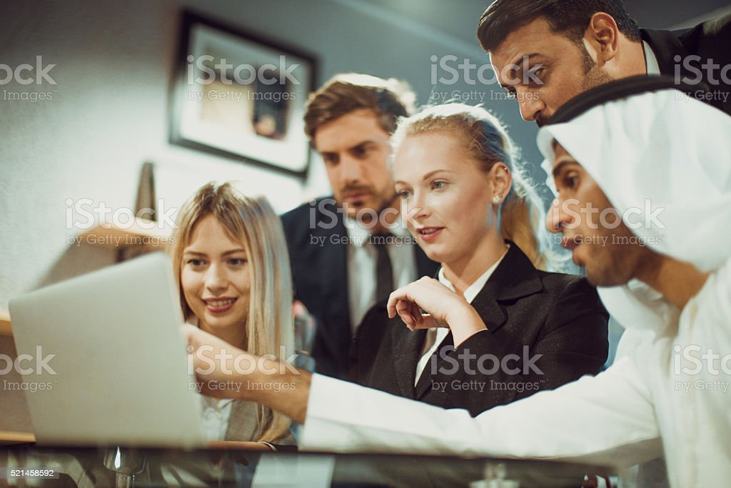 Discussion on a laptop between multicultural business professional stock photo