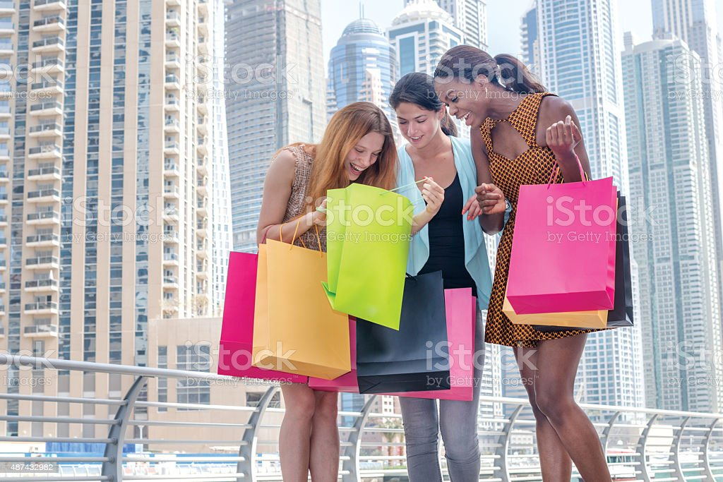 Discussion purchases. Beautiful girl in dress holding shopping b stock photo