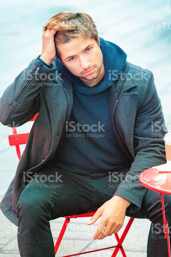 Disgruntled young man sitting bothered expression stock photo