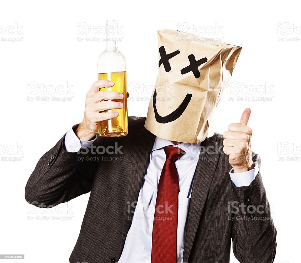 Disguised by paper-bag mask with drunken eyes, businessman lifts bottle stock photo