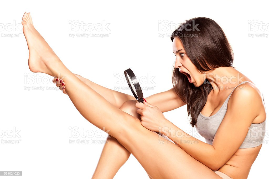 Disgusted girl looking at hair on her legs stock photo