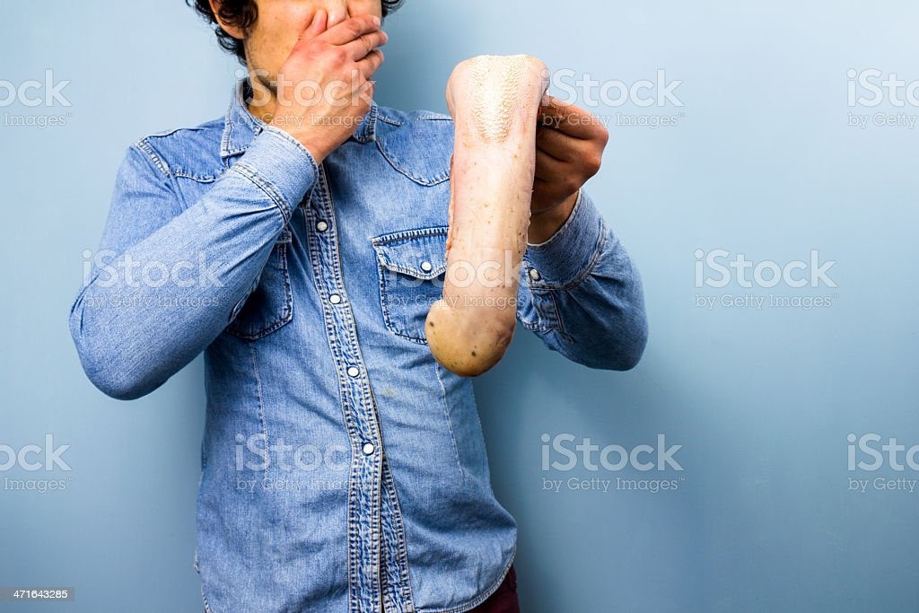 Disgusted man holding a raw ox tongue stock photo