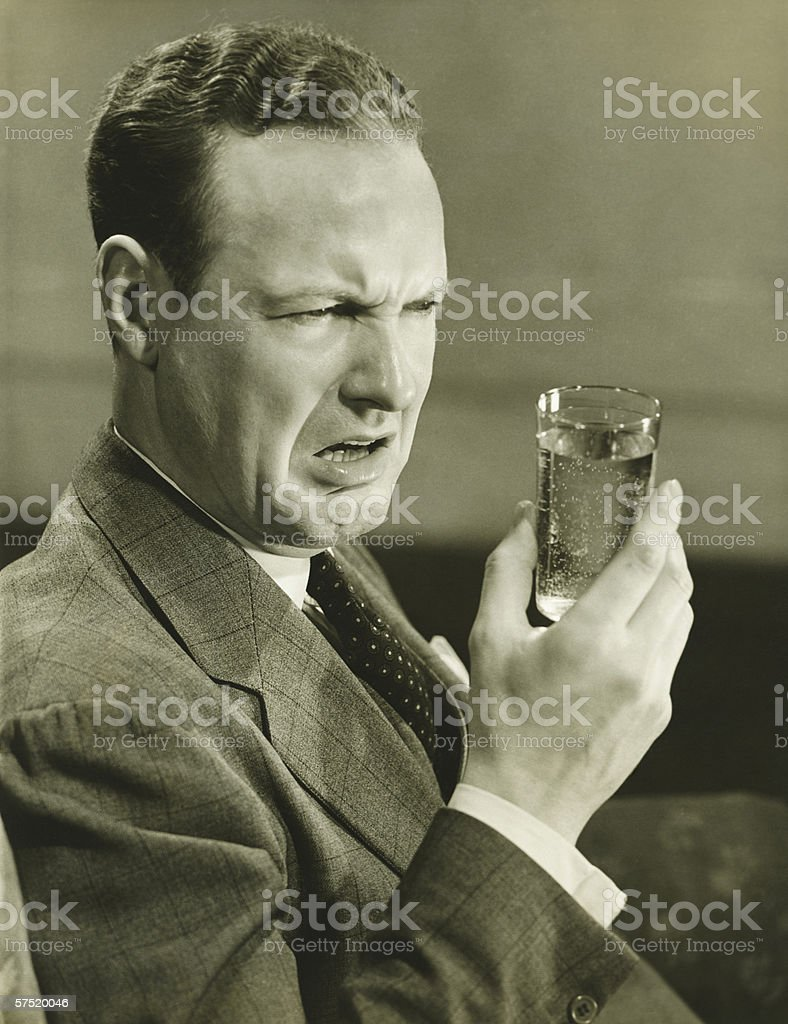 Disgusted man looking at glass of water, (B&W) stock photo