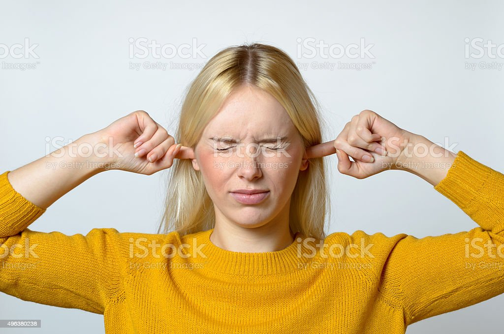 Disgusted Woman Covering her Ears with Fingers stock photo