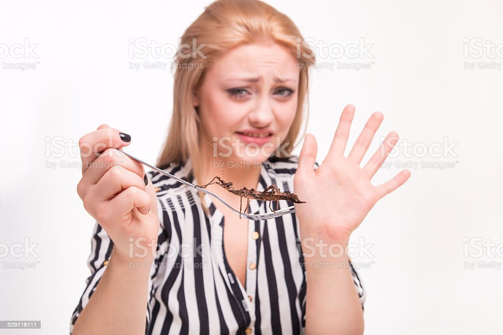 Disgusted woman eating insects with a fork in a restaurant stock photo