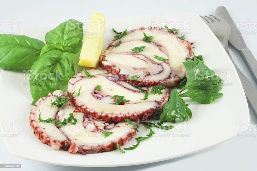 A dish of octopus carpaccio with basil and a lemon slice stock photo
