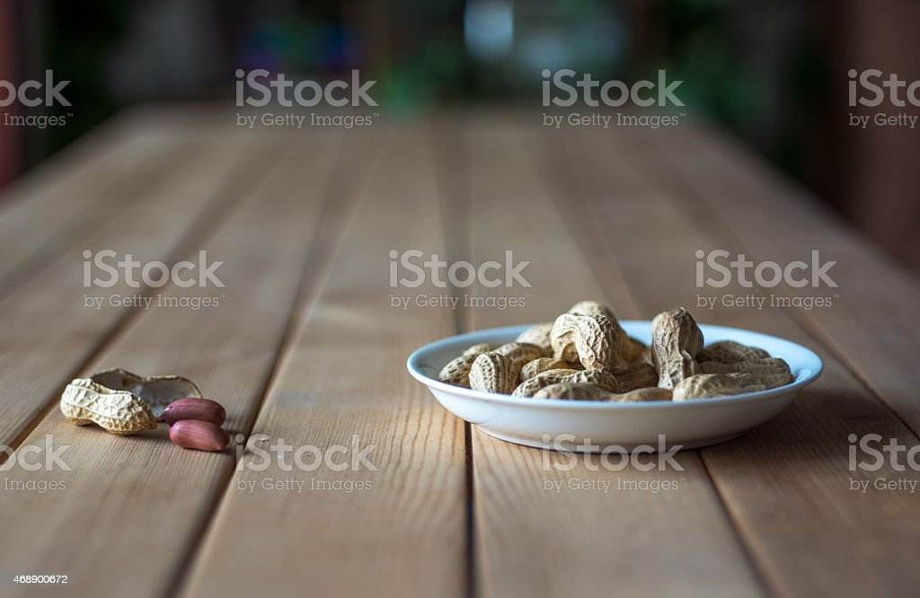 dish of peanuts on wooden table stock photo