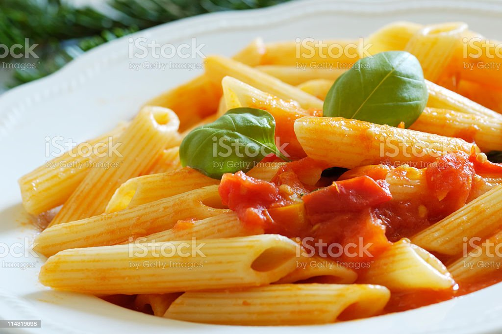 Dish of penne pasta with tomato sauce garnished with basil stock photo