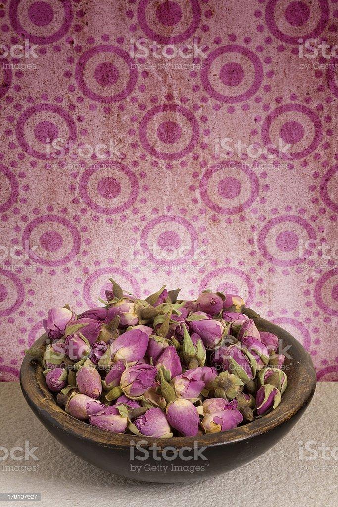 Dish of rosebud pot pourri set against dirty old wallpaper stock photo