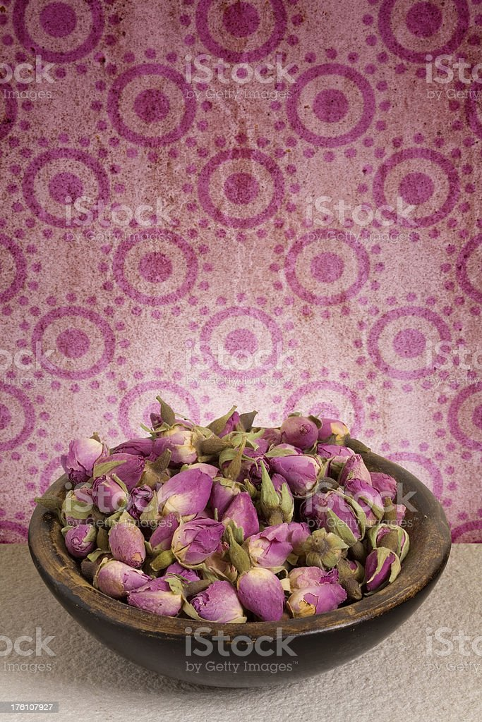Dish of rosebud pot pourri set against dirty old wallpaper stock photo