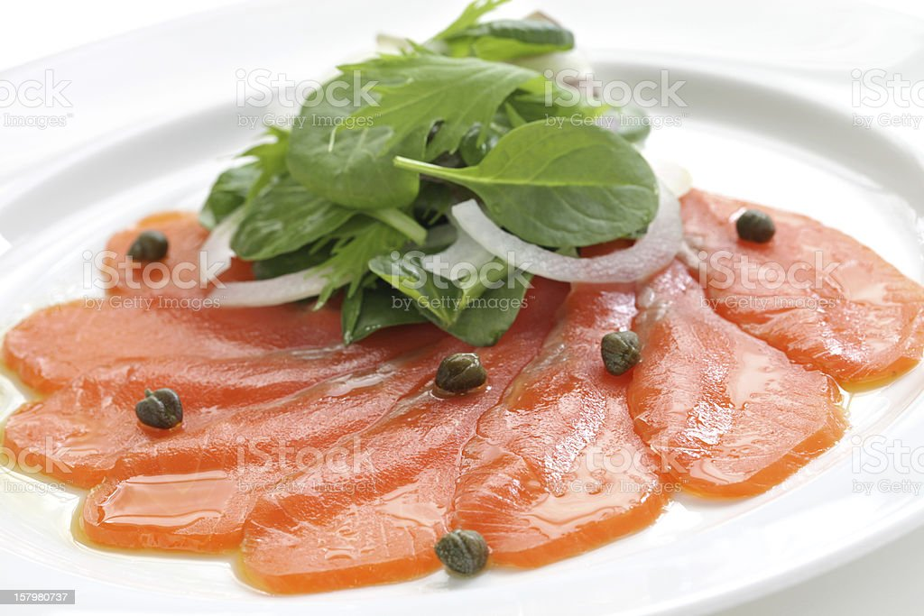 A dish of sliced smoked salmon with a garnish and capers stock photo