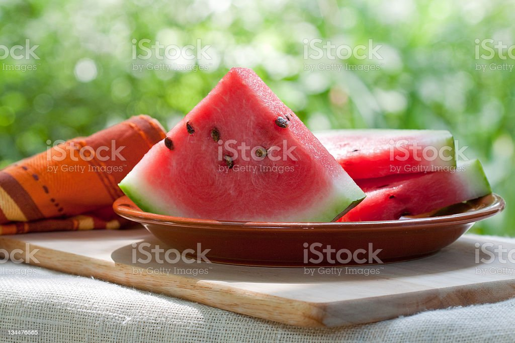 Dish of sliced watermelon slices on brown dish outdoors stock photo