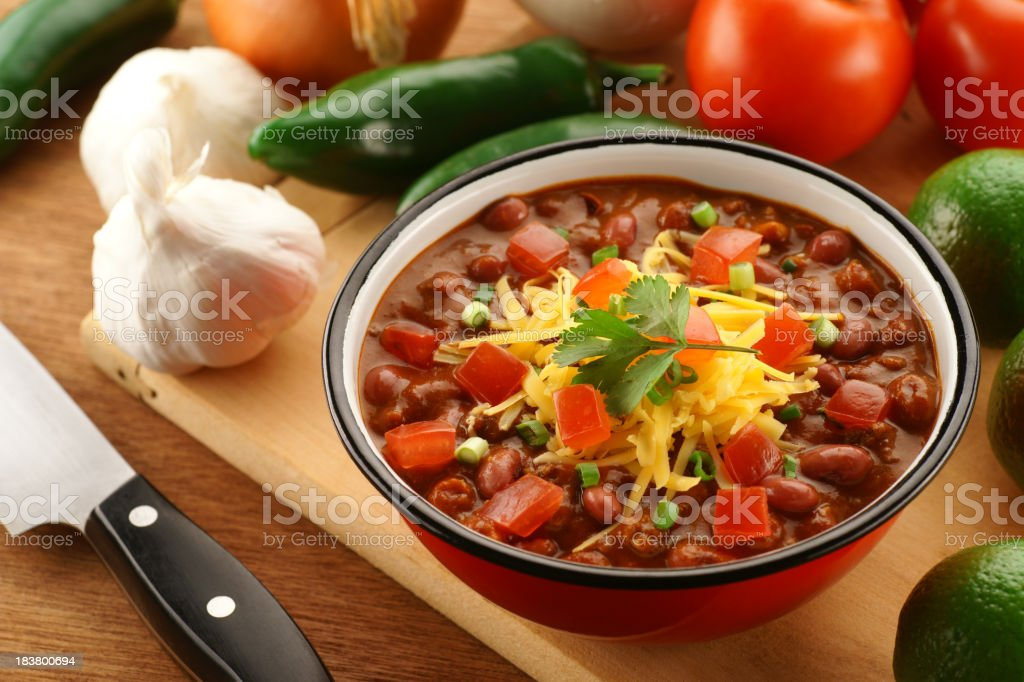 A dish on top of a cutting board with surrounding vegetables stock photo