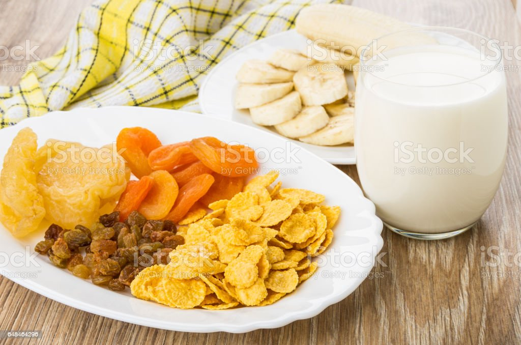 Dish with dried fruits,glass milk, slices of bananas stock photo