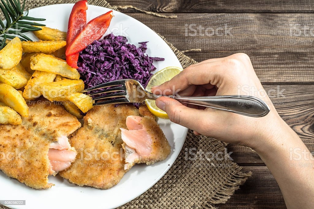 Dish with fried salmon, potatoes and vegetables. Hand holding fork. stock photo