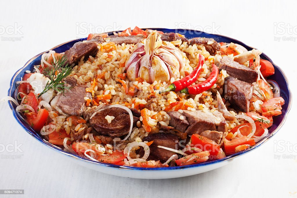 dish with pilaf Uzbek dishes, garlic, onions, carrots, tomatoes, beef stock photo