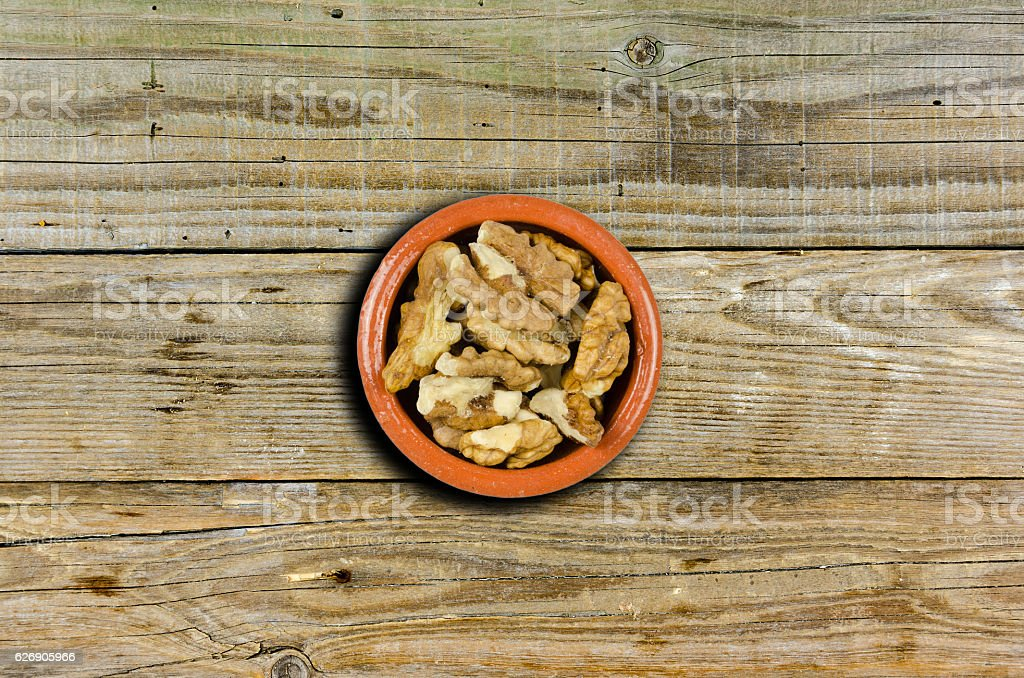 dish with walnuts  on wooden background stock photo