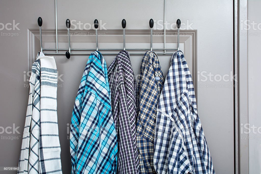 dishcloth and four casual men shirts on a clothes rack stock photo