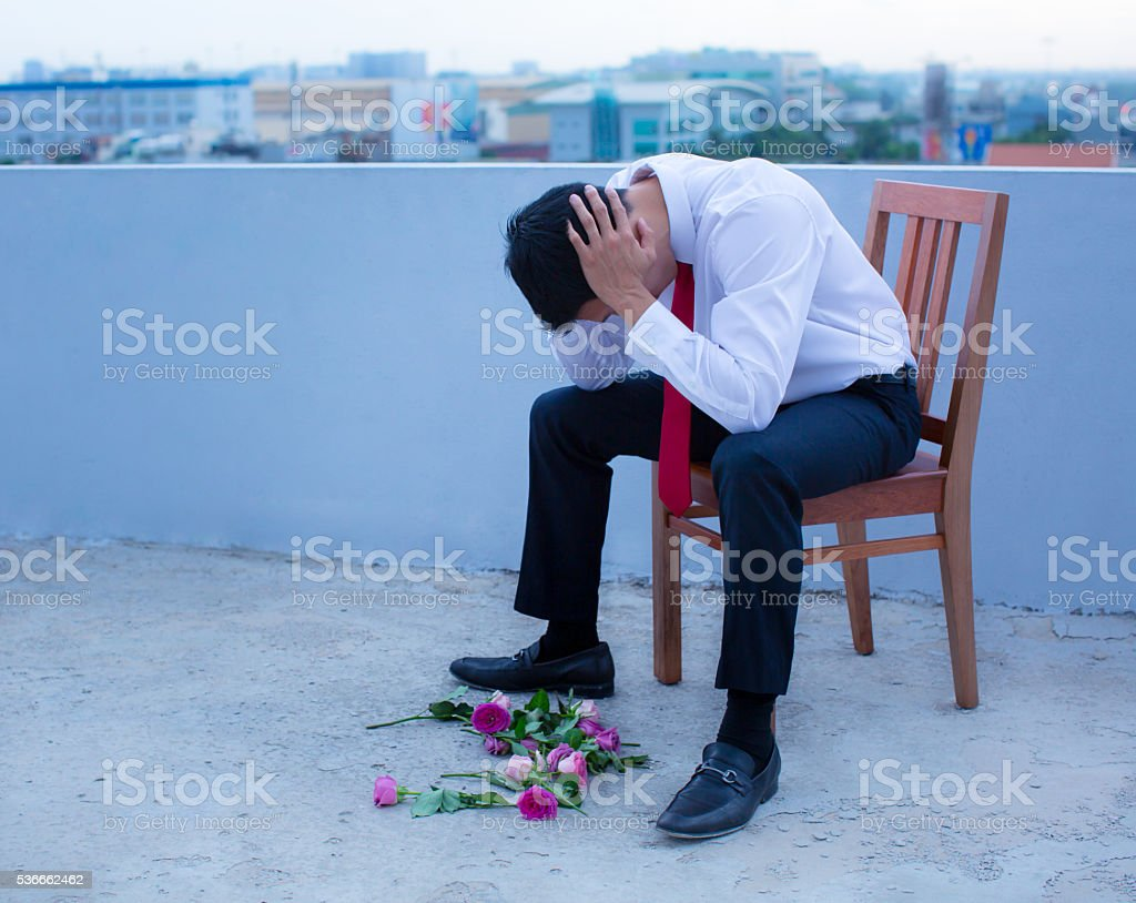 Disheartened man in a suit, broken-hearted after being rejected. stock photo