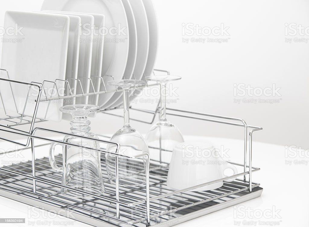 Dishes and glasses drying on metal dish rack stock photo