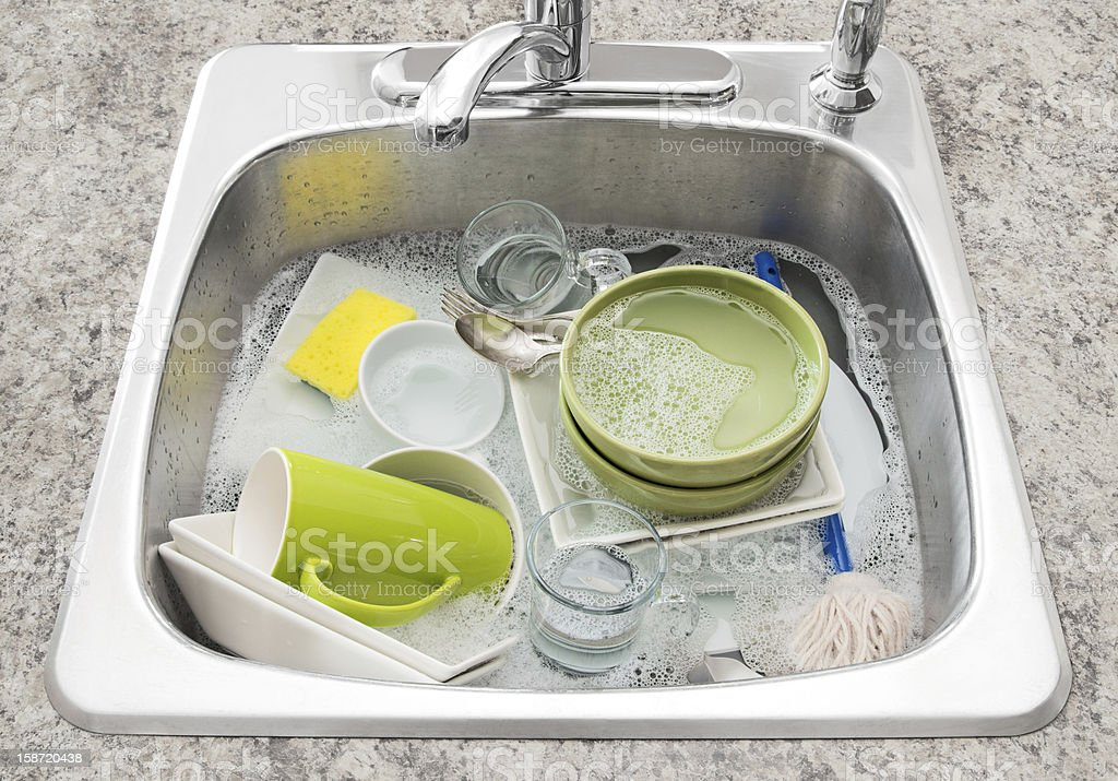 Dishes soaking in the kitchen sink stock photo