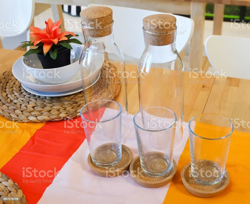 Dishes with Glass and Glass Bottle on Table stock photo