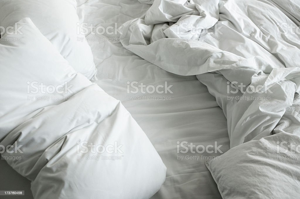 Disheveled sheets and pillows of an unmade bed stock photo