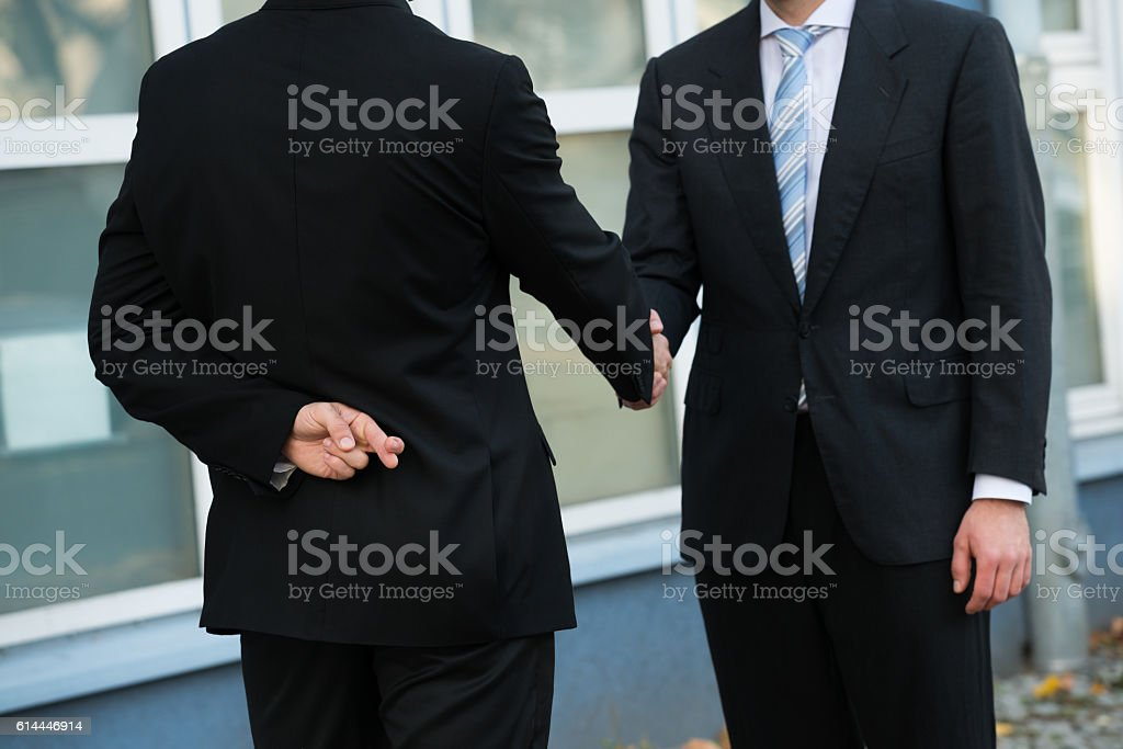 Dishonest Businessman Shaking Hands With Partner stock photo
